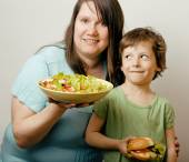 Mature fat woman holding salad and little cute boy with hamburger teasing — Stock Photo
