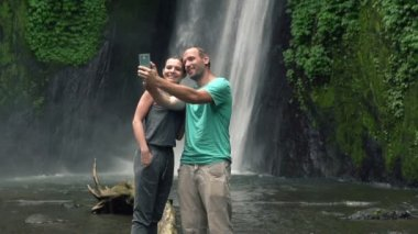 Couple taking photo by waterfall — Stock Video