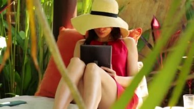 Woman with tablet relaxing in gazebo — Stock Video