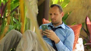 Man texting on smartphone in gazebo — Stock Video