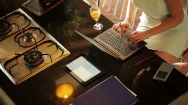 Businesswoman working on laptop in kitchen — Stock Video