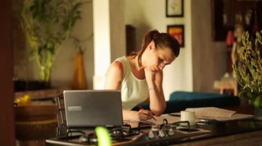 Businesswoman writing notes in documents in kitchen — Vidéo