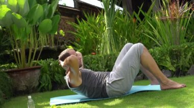 Man doing sit-ups on mat in garden — Wideo stockowe