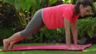 Young woman exercising on mat — Стоковое видео
