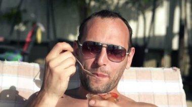 Man on sunbed eating ice cream — Stock Video