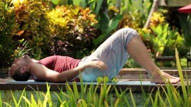 Handsome man exercising sit-ups in garden — Stock Video
