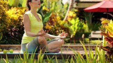 Attractive woman meditating in garden — Stock Video