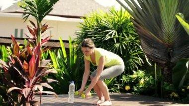 Woman exercising with dumbbells in garden — Stock Video