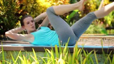 Woman doing sit-ups exercise in garden — Stock Video