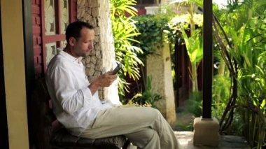 Man med smartphone sitter på bänken — Stockvideo