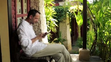 Man with tablet sitting on bench — Stock Video