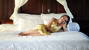 Woman lying and talking on cellphone — Stock Video