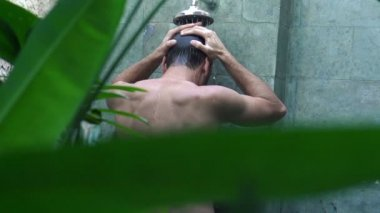 Young man taking shower outdoors — Stock Video