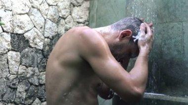 Man washing hair under shower — Stock Video