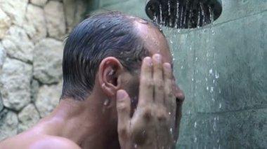 Man washing face under shower — Stock Video