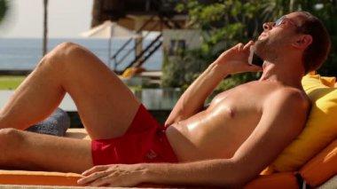 Man talking on cellphone lying on sunbed — Stockvideo