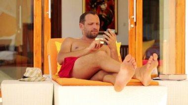 Homem com smartphone relaxando no solário — Vídeo stock