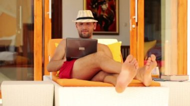 Man with laptop lying on sunbed — Stock Video