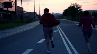 Couple jogging on road in evening — Video Stock