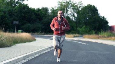 Jogger running on asphalt road — Stok video