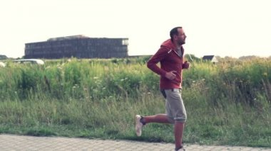 Jogger running in countryside — Wideo stockowe