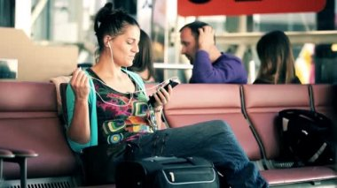 Attractive young woman listening music on smartphone at airport — Stock Video