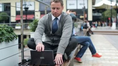 Businessman finish work on laptop and relax in the city — Stock Video