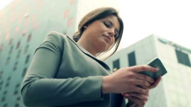 Pretty businesswoman texting on smartphone in the city — Stock Video