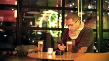 Young man with smartphone drinking beer in bar late at night — Stock Video