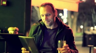 Man with tablet computer drinking beer in bar — Stock Video