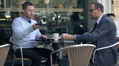 Two businessmen with tablet computer talking and drinking coffee in cafe — Stock Video
