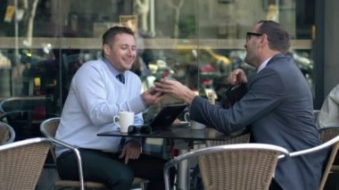 Two businessmen looking at something funny on smartphone in cafe — Stock Video