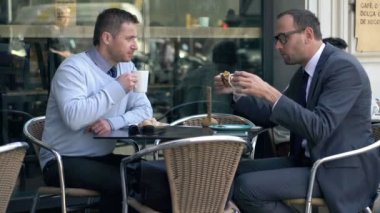 Two businessmen talking during lunch, coffee break in cafe — Stock Video