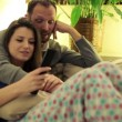 Young couple on sofa watching tv at home — Stock Video #61865405