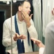 Businessman applying moisturizing cream on his face in bathroom — Stock Video #61868269