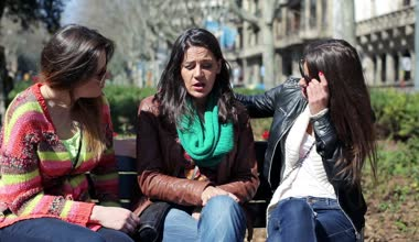 Girlfriends comforting their sad friend on bench in the city — Vídeo de Stock