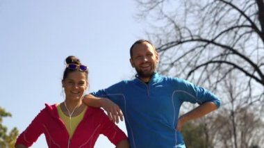 Happy sporty joggers, couple standing in park — Vídeo de stock