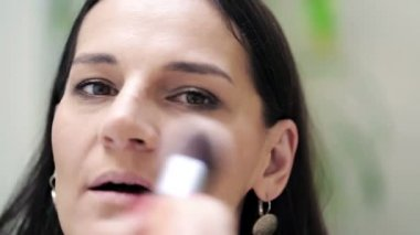 Young woman applying makeup with brush on her face — Vidéo