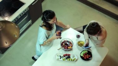 Two girlfriends talking, laughing by the table in kitchen at home — Stock Video
