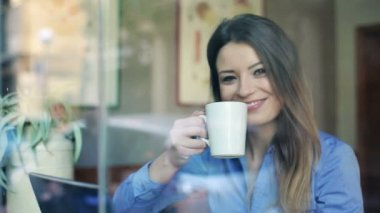 Happy businesswoman drinking coffee by counter in cafe — Stock Video