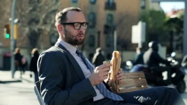 Young handsome businessman eating baguette by the city street — Stock Video