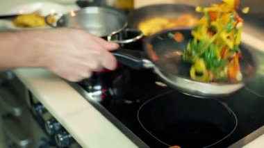 Cook flipping vegetables on frying pan in the kitchen — Stock Video
