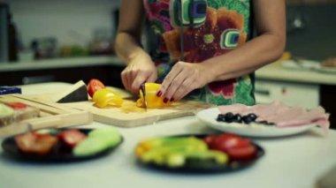 Woman slicing yellow pepper, preparing breakfast in kitchen — Stock Video