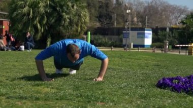 Young man doing press ups in the park — Stock Video