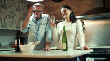 Young couple raising toast with wine, celebrating in kitchen at home — Stock Video