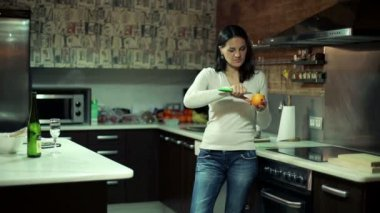 Young woman peeling orange in kitchen at home — Stock Video