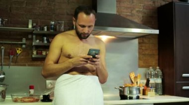 Man texting on smartphone and drinking coffee after shower — Stok video