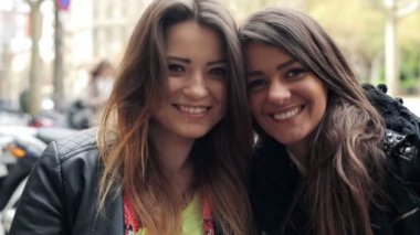 Portrait of two happy beautiful girlfriends in the city — Stockvideo