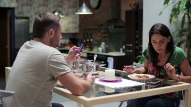 Couple using smartphones during dinner at home — Stock Video