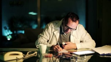 Doctor writing rx prescription at office late at night — Wideo stockowe